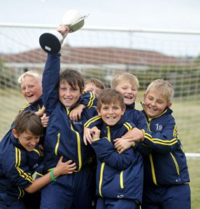 FOOTBALL --- North Walney Primary School Year 5 and 6 football team who were named champions in the Danone Small Schools 7-a-side national school finals in Lilleshall National Sports Centre.// Pictured: Captain Gary Ferguson lifts the cup with his team-mates (Not pictured is Jonty O'Neill) Tuesday 16th June 2015. LINDSEY DICKINGS REF: 50078078B004.jpg